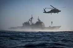 The guided-missile cruiser USS Monterey (CG 61) and a MH-60R Sea Hawk helicopter assigned to Helicopter Maritime Strike Squadron Forty-Eight (HSM) 48 conduct search and rescue training evolution.