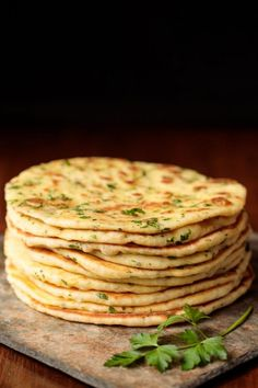 Photo of a stack of Greek Yogurt Turkish Flatbread (Bazlama) on a slate surface with a sprig of cilantro in the foreground.