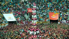 """In Tarragona, Spain, thousands of people gather to witness one of humanity's strangest and most spectacular contests: building the human towers of Catalonia. Adorned in colorful costume, hundreds of """"castellers,"""" or tower builders, form elaborate human structures that soar into the sky. Containing up to 10 tiers and rising nearly 50 feet high, sometimes, the towers do fall …"""