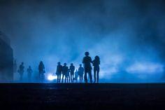 Performance im Nebel 02 – Beunruhigende Performance in Blau: Menschen nachts im Scheinwerferlicht. Hunde bellen. Der Nebel zeichnet in der Tiefe unterschiedliche Schärfen und Tonwerte. 2013, MD | © www.piqt.de | #PIQT
