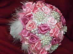 Buquê de broches feito com rosas de cetim em tons cor de rosa. Plumas e renda no cabo.