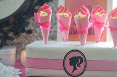 Wrap a shoe box (or soup can box) in fancy wrapping paper. Make X's with exacto knife. Perfect for holding pops or popcorn cones. Add the free printable and some ribbon and you're set! #GirlsBarbieBirthday Party