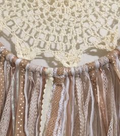 This handmade boho inspired dream catcher would make a great accent to any space!  Hoop with cream colored macramé doily: 10.5 diameter Beige, white, and brown fabrics and ribbons: approx. 12 Total length: approx. 22