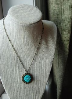 "Turquoise Princess $10 This youth's necklace is 15"" long in antiqued brass chain, setting and finding with a acrylic cabochon flower for a splash of turquoise. The perfect addition to spring or summer attire.  Nickel and lead free."