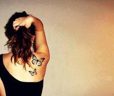 Pequeño tatuaje de dos mariposas en la espalda.