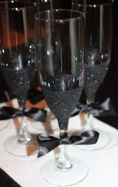 DIY Toasting Flutes - Take simply champagne flutes and add glitter around the base with a ribbon tied around the stem!