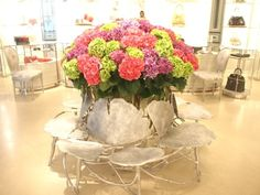fresh hydrangea and silver lily pad seating at Dior store..