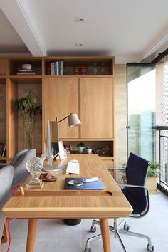 Decoração de apartamento integrado e com crianças. No home office luz natural, cadeira preta, escrivaninha de madeira e estante de madeira.