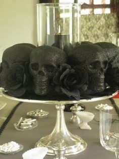 Dollar store skulls with black glitter on a cake platter as a centerpiece. I love the gothic addition of black roses. #Halloween #Party #ideas