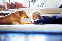 woman and dog looking at each other eye to eye on living room floor love