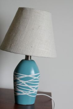 DIY Lamp remodel. 1. Wrap Rubber Bands around base 2. Spray paint in any color 3. Allow to dry completely and remove rubber bands to reveal original color.
