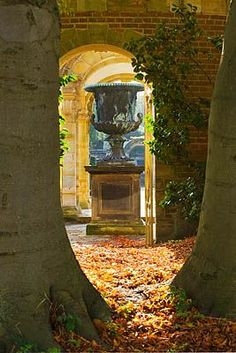 HEVER CASTLE, KENT: AUTUMN: VIEW FROM OUTSIDE THE ITALIAN GARDEN THROUGH TREES TO HUGE URN/ CONTAINER IN THE ITALIAN GARDENS