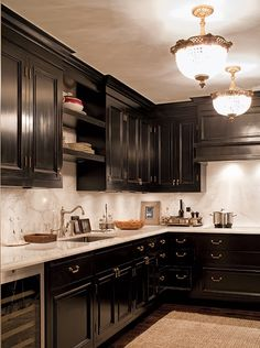 Black kitchen cabinetry with gold hardware. White marble countertops and backsplash.