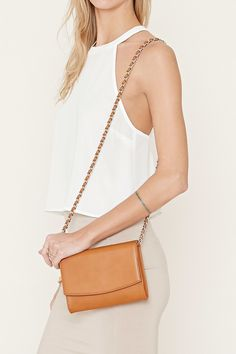 A faux leather crossbody bag featuring a chain-trimmed shoulder strap, a fold-over front flap, and a snap-buttoned front closure.