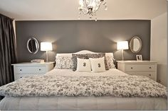 Gray accent wall and white linens, white bedside tables, silver mirrors, chandelier in bedroom
