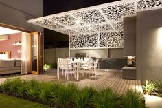 Contemporary out door entertaining area complete with a BBQ, fireplace and a white Gingko patterned laser cut pergola screen designed by Ian Barker Garden Design.