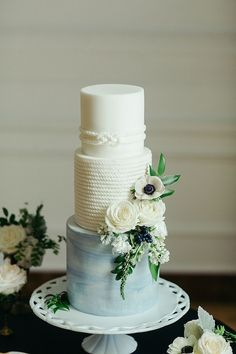 White and light blue nautical-inspired wedding cake with floral details.