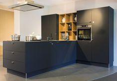 Keuken Pronorm T-opstelling in zwart mat lak met een RVS gematteerd, 4 mm dik, werkblad. Een niet veel voorkomende opstelling: een unieke moderne keuken.