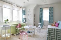 Contemporary girl's bedroom features a green print daybed dressed in blue shams facing a play space.