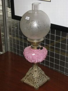 An antique oil lamp, metal base & pink glass reservoir and