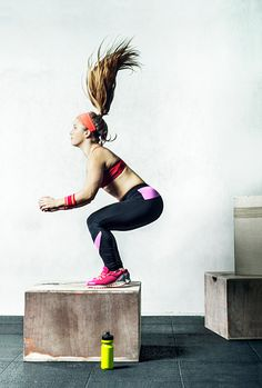 Stock Photo : Athletic crossfit woman jumping on a wooden box