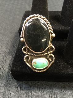 WONDERFUL STERLING SILVER RING DONE IN TURQUOISE AND BLACK ONYX WITH S ROPE DESIGN AROUND EDGES. RING SIZE IS 10.