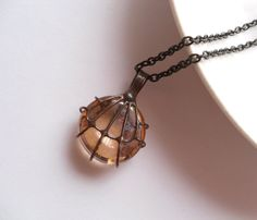 Copper wire and glass lens pendant. Copper wire mesh soldered around the beige glass lens. Glass lens are made by hands, so they are…