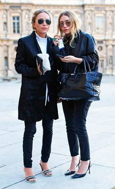 Mary-Kate e Ashley Olsen look black and white de jeans, camiseta e mantô preto.