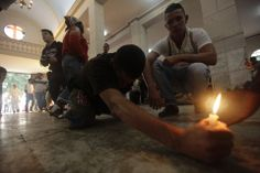 PROSTRATE: A man held a candle as part of an offering at the shrine of St. Lazarus in Rincon, Cuba, Tuesday. The annual pilgrimage to one of...