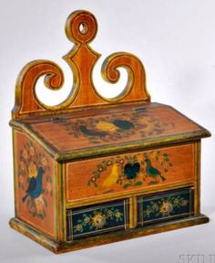 "Skinner's - Ellie Hoover Collection. August 9, 2015 Lot 1107. Estimate: $12,000-18,000. Realized: $58,425 !! Description: Carved and Painted Pine Hanging Spice Box, Samuel L. Plank (Mifflin County, 1821-1900), Pennsylvania, last quarter 19th century, with scroll-carved backsplash over two drawers, the rectangular lift-top opens to a divided interior, original decoration of blue and yellow birds and roses on an ochre ground, pencil inscription on the back reads: ""Manufactured by ..."