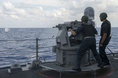 Command Master Chief Mark Schlosser fires an MK-38 25mm machine gun aboard the guided-missile destroyer USS Donald Cook (DDG 75) during a live-fire gunnery exercise.