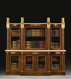 A Royal Regency ormolu-mounted burr-yew breakfront bookcase - Supplied to George, Prince of Wales for Carlton House, London, by Marsh  Tatham in 1806, probably to a design by Charles Heathcote Tatham, surmounted by four masks of Bacchus on a draped plinth with a statuary marble top, the frieze decorated with adorsed lyre motifs  anthemia over three glazed doors, the upper section with the Windsor Castle 1866 inventory brand, 6ft. 1in., 6ft. 1¼in., 1ft. 8¼in.