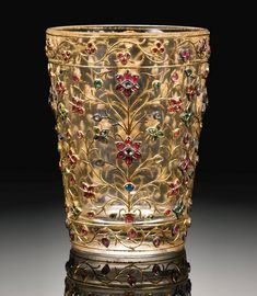 A Mughal gem-set rock crystal cup, India, circa 18th century; the rock crystal carved in the form of a cup, set with gold floral tendrils highlighted with rubies, emerald and diamonds .11.3cm. height, 8.5cm. diam.