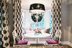 dining room that's neutral with punches of pink and pattern. Dark grey walls with beige curtains and white table.