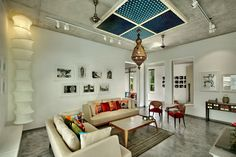 Living room with heavy ceiling made out of r.c.c. and wooden element with track light and decorative element .