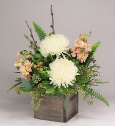 footballs and stock: a wooden cube vase with ivory football mums, peach stock and hypericum berries, white waxflower, textured greenery and pussy willow.