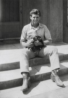 "Joe Jr. holding two puppies at the Jay-6 Ranch, Arizona, circa 1936. The original notation that appeared on this photograph was: ""Said to be Kathleen Kennedy's favorite photograph JPK Jr."""
