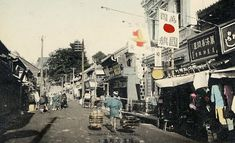 A vendor carrying his merchandise walks by shops in Motomachi, Yokohama, Kanagawa Prefecture. Kanagawa Prefecture, Japan Landscape, Retro Pictures, Meiji Era, Old Photography, Yokohama, Asia Travel, Vintage Images, Old Photos