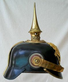 Right side view of a German WWI infantry officer's pickelhaube with tall spike: Eagle on top of clasped scepter, orb in other claw. Eight metal rosettes on base of spike with pearl ring surround. Personalized on the inside of the liner, reads Leutn. Bromme.
