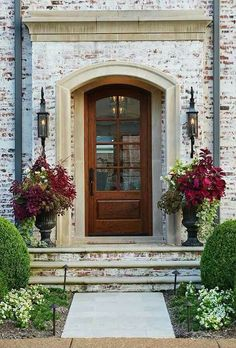 Love the rich burgundy florals paired with the dramatic matte black urns in front of the light stone home exterior.