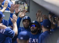 Prince Fielder #84, right, of the Texas Rangers and Elvis Andrus #1 of the Texas Rangers are congratulated by teammates in the dugout after scoring on a single by Ian Desmond #20 of the Texas Rangers during the sixth inning  at Safeco Field on June 12, 2016 in Seattle, Washington. (Photo by Stephen Brashear/Getty Images)