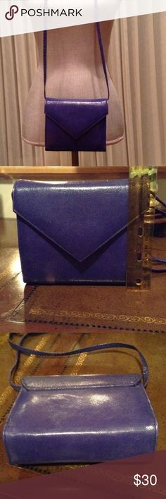 "Pre-Loved Purple Leather Handbag This is a vibrantly royal purple leather handbag. It is Pre-Loved, having been carried numerous times, so it does show some signs of wear, including minor indentations on the anterior that the camera was unable to capture. There is also some cracking on the interior (see 4th picture). Magnetic snap closure. Shoulder strap measures approximately 48"" long. Purse measures approximately 5"" tall x 6"" wide x 1.5"" deep. This is a stunning handbag that's great for…"