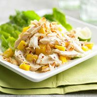 Mango Chicken Salad with Coconut Recipe:3 skinless, boneless chicken breast halves 2 limes 1 cup unsweetened coconut milk 1 tablespoon soy sauce 1/2 teaspoon crushed red pepper 1/2 cup flaked unsweetened coconut 2 mangoes, seeded, peeled and chopped   Lettuce leaves (optional)