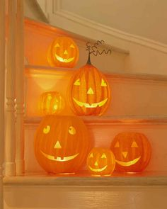 The stairway in an entry hall is an appropriate spot to display graduated sizes of handmade paper jack-o'-lanterns. For safety, these beaming faces are lit from within by battery-powered lights. A single sheet of tissue pasted inside diffuses the light and hides the working parts.