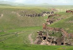 """A gorge below Ani, showing numerous caves dug into cliffs, as well as fortifications. A modern border fence can be seen at bottom center, Armenia is on the left, Turkey, on the right, photographed on June 8, 2011. Original <a target=""""_new"""" href=""""http://www.flickr.com/photos/adam_jones/5812397736/"""">here</a>."""