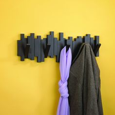 Sculptural and functional, the Sticks wall-mount multi hook rack from Umbra offers ample storage for coats, bags, accessories and more. Constructed of molded wood with an espresso brown finish, Sticks features five sturdy hooks that flip up when not in use, creating a clean, seamless profile that's great for tight spaces or minimalist decor styles. Concealed mounting hardware is included. Designed by Umbra Studio for Umbra original, modern, casual, functional and affordable design for the...