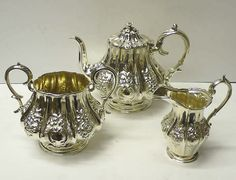 Antique Silver Tea Set  A decorative 3 piece sterling silver tea set with chased flowers and the teapot having a pretty flower finial. The jug and bowl have the original gilt interior. Teapot and bowl Sheffield 1854, maker Roberts & Slater. Jug London 1849, maker Richard Pierce & George Burrows.  Price 1,575 British pounds