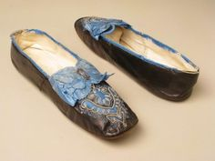 1860s bronzed kid chameleon slippers (having cutouts revealing contrasting silk, edged with tambour embroidery). Lined with linen and kid. Blue silk ribbon binding, large bow, and rosette topped with tiny decorative buckle. Made by Julien Mayer, Paris. Manchester Galleries.