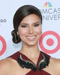 This side bun on Roselyn Sanchez is modern and pretty. Add anti-frizz gel to damp hair and blow-dry straight. Brush hair from one temple over to the opposite ear, creating a smooth surface of hair all around. Gather hair at ear temporarily. Smooth over hair once again with shine serum and secure side ponytail tightly. Twist into a bun and pin in place. Finish with hairspray.
