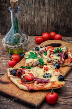 flavorful homemade pizza with bacon - hunk of delicious meat pizza with bacon and olives on the background of the vegetables.The image is tinted